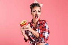 Aufgeregte überraschte junge Stift-obenfrau, die Pommes-Frites hält lizenzfreie stockfotos