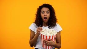 Aufgeregte afro-amerikanische Frau, die Popcorn isst und interessanten Film aufpasst lizenzfreie stockfotos