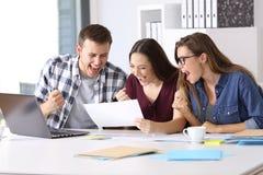 Aufgeregte Arbeitskräfte, die einen guten Ergebnisbericht lesen lizenzfreie stockbilder