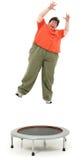 Aufgeregte beleibte Vierziger-Frau, die auf Trampoline springt Lizenzfreie Stockbilder
