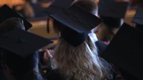 Aufgeregte blonde Frau in der schwarzen Rede des Kleider- und der Kappeapplaudierenden Lehrers stock video footage