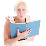 Aufgeregte blonde Frau, die ein Buch liest Lizenzfreies Stockbild