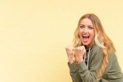 Aufgeregte blonde Frau, die ihre Fäuste zusammenpressend zujubelt Lizenzfreies Stockfoto