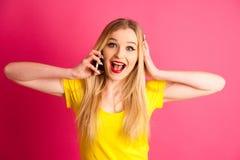 Aufgeregte blonde Jugendliche, die am intelligenten Telefon über rosa BAC spricht Lizenzfreies Stockfoto