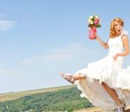 Aufgeregte Braut auf Landhügel stockfoto