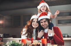 Aufgeregte Eltern, die neues Jahr mit reizender Tochter feiern lizenzfreie stockbilder