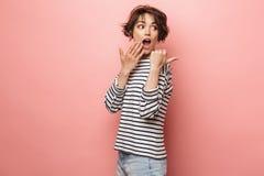 Aufgeregte entsetzte überraschte Schönheitsaufstellung lokalisiert über dem rosa Wandhintergrundzeigen stockfoto