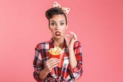 Aufgeregte entsetzte junge Stift-obenfrau, die Pommes-Frites hält stockbild