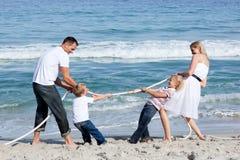 Aufgeregte Familie, die Tauziehen spielt