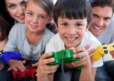 Aufgeregte Familie, die Videospiele spielt Stockfotografie
