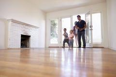 Aufgeregte Familie erforschen neues Haus an beweglichem Tag Stockfoto