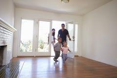 Aufgeregte Familie erforschen neues Haus an beweglichem Tag Lizenzfreie Stockfotografie
