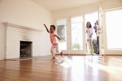 Aufgeregte Familie erforschen neues Haus an beweglichem Tag Stockfotografie