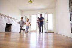 Aufgeregte Familie erforschen neues Haus an beweglichem Tag Stockbilder
