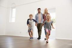 Aufgeregte Familie erforschen neues Haus an beweglichem Tag Lizenzfreie Stockfotos