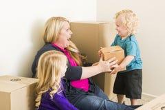 Aufgeregte Familie im leeren Raum, der mit beweglichen Kästen spielt Stockfotografie