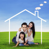 Aufgeregte Familie mit einem Traumhaus am Feld Stockfotos
