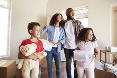 Aufgeregte Familien-tragende Kästen in neues Haus an beweglichem Tag lizenzfreie stockfotos