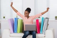 Aufgeregte Frau beim online kaufen lizenzfreies stockfoto