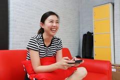 Aufgeregte Frau, die auf Steuerknüppel im Raum spielt stockfotos