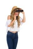 Aufgeregte Frau, die durch Ferngläser schaut Lizenzfreie Stockfotos