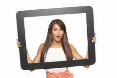 Aufgeregte Frau, die durch Tablettenrahmen schaut Stockbilder