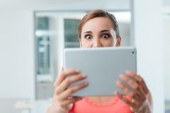 Aufgeregte Frau, die eine Tablette hält Lizenzfreies Stockfoto