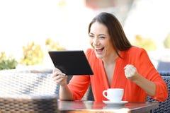 Aufgeregte Frau, die on-line-Angebote auf Tablette in einer Stange findet stockfotografie