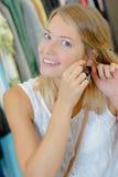 Aufgeregte Frau, die nach innen auf neuen Ohrringen versucht Stockfotos