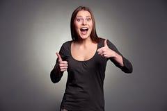 Aufgeregte Frau, die sich Daumen zeigt Lizenzfreie Stockfotos