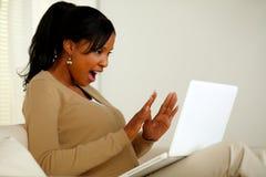 Aufgeregte Frau, die zum Laptopbildschirm schaut Stockbild