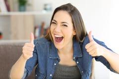 Aufgeregte Frau mit den Daumen oben zu Hause lizenzfreies stockbild