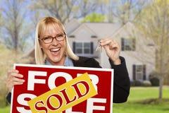 Aufgeregte Frau mit Verkaufszeichen und Schlüsseln vor Haus Stockbilder