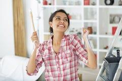 Aufgeregte Frau nach der Fertigung des Malens stockfoto