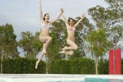Aufgeregte Frauen, die in Pool springen Lizenzfreie Stockfotos