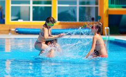 Aufgeregte Freunde, die Spaß im Pool, Wasserkampf haben Stockbilder