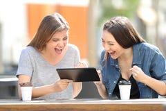 Aufgeregte Freunde, die Tabletteninhalt in einem Park aufpassen lizenzfreie stockfotografie