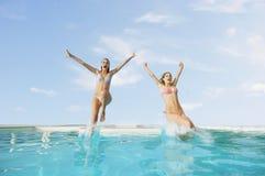 Aufgeregte Freundinnen, die in Pool springen Stockbilder