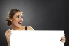 Aufgeregte Frau, die leeres Brett hält Stockfoto