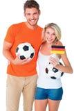 Aufgeregte Fußballfanpaare, die an der Kamera zujubeln Stockfotografie