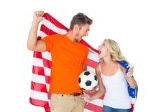 Aufgeregte Fußballfanpaare, die USA-Flagge halten Stockfotografie