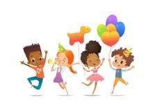 Aufgeregte gemischtrassige Jungen und Mädchen mit den Ballonen und den Geburtstagshüten, die glücklich mit ihren Händen oben spri lizenzfreie abbildung