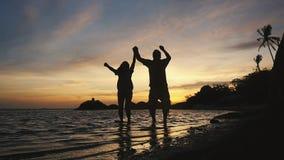 Aufgeregte glückliche zujubelnde Paare, die auf tropischen Strand bei Sonnenuntergang am Sommerreise-Ferienfeiertag springen Lang stock video