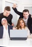Aufgeregte glückliche Gruppe Freunde, die online unter Verwendung des Laptops gewinnen Stockfotografie