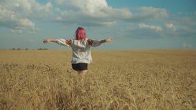 Aufgeregte hübsche Frau, die auf dem Weizengebiet sich freut stock footage