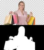 Aufgeregte hübsche junge Dame, die die Kamera zeigt Einkaufstaschen, Alpha Channel schauend steht stockfotos