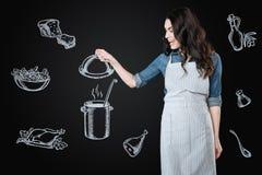 Aufgeregte Hausfrau, welche die geschmackvolle Suppe beim Kochen sie betrachtet Lizenzfreie Stockfotografie