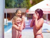 Aufgeregte Jugendfreunde unter Sommerdusche Stockfotos