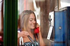 Aufgeregte junge Frau in der Telefonzelle im Freien Stockbilder