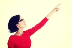 Aufgeregte junge Frau, die auf Exemplarplatz zeigt Lizenzfreie Stockfotografie